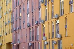 Färga fasaden av ett hus med lotten av luftvillkorenheter Arkivbild