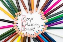 Färga håller blyertspennor i cirkelordning med meddelandeTANGENT att utbilda sig arkivbilder