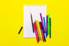 Färga markörer och en anteckningsbok på en gul bakgrund Arkivfoto