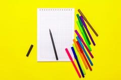 Färga markörer och en anteckningsbok på en gul bakgrund Royaltyfri Fotografi