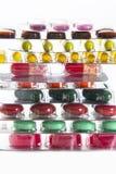 Färga minnestavlor, kapslar och vitaminer i blåsor på den vita bakgrunden Arkivbilder