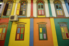 Färga stänger med fönsterluckor och färgar facaden av byggnad i lite Indien, syndar Royaltyfri Bild