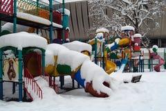 Färgad lekplats i vinter, med modern byggnad i bakgrund royaltyfria foton