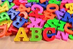 Färgad plast- märker abc:et på en träbakgrund Fotografering för Bildbyråer