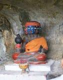 Färgad staty i en grotta Arkivbilder