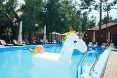 Färgad uppblåsbar enhörning för regnbåge som svävar i en simbassäng i sommaren Vit uppblåsbar enhörning i pölen arkivbild