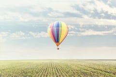 Färgad varmluftsballong som flyger över ett lantligt landskap arkivbilder