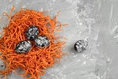 färgade ägg med den svartvita geometriska modellen i ett dekorativt orange rede på en konkret bakgrund arkivfoton