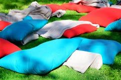 Färgade överkast och kuddar ligger på det gröna gräset parkerar in fotografering för bildbyråer