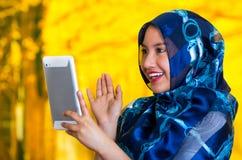 Färgade bärande blått för härlig ung muslimkvinna hijab, den hållande övre minnestavlan som stirrar på skärmen, höstskogbakgrund royaltyfri bild