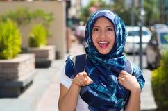 Färgade bärande blått för härlig ung muslimkvinna hijab som pekar fingret som ler, utomhus stads- bakgrund arkivbild