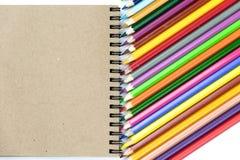 Färgade blyertspennor, anteckningsböcker på brun och beige bakgrund Br?nnm?rka brevpappermodellplats, anm?rker mellanrumet f?r at royaltyfria bilder