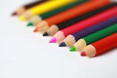 Färgade blyertspennor för skolatillförsel i rad, isolerat Arkivbild