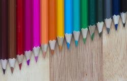 Färgade blyertspennor mot en träbakgrund Fotografering för Bildbyråer