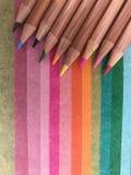 Färgade blyertspennor på färgat papper arkivbild