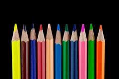 Färgade blyertspennor på svart bakgrund Royaltyfria Foton
