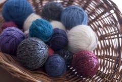 Färgade bollar av ull i korg Royaltyfria Foton