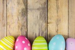 Färgade easter ägg på en träbakgrund arkivfoto