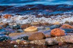 Färgade kiselstenar på shorelinen med vatten och vågor royaltyfri foto