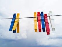 Färgade klädnypor som fästas till klädstrecket för att torka arkivbilder