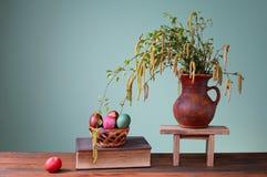 Färgade påskägg, böcker och blommor i en vas arkivfoton