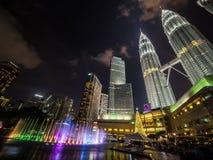 Färgade springbrunnar framme av de Petronas tornen och den Suria KLCC gallerian Royaltyfri Bild