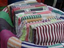 Färgade textiler som är till salu utanför en shoppa i Essaouira, Marocko royaltyfri foto