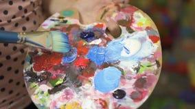 Färgar blandande akryl för den kvinnliga konstnärhanden med borsten på en palett stock video