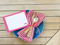 Färgar den utomhus- tabellen Placesetting för sommarpicknicken med röd vit och blått med gaffeln och skeden med ett tomt kort för arkivfoto