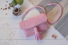 Färgar handgjorda rosa färger för kvinnlig handväska på en vit bakgrund med a Arkivfoto