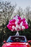 Färgballongerna och den röda bilen Arkivbilder