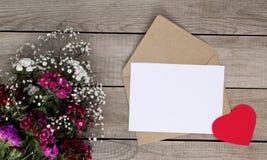 Färgblommor, hjärtaform och kuvert på träbakgrund valentin för dag s fotografering för bildbyråer