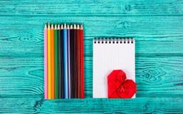 Färgblyertspennor, anteckningsbok och hjärta av origami på en blå bakgrund Brevpappertillbehör Royaltyfri Bild