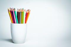 Färgblyertspennor i en vit rånar Arkivbild