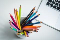 Färgblyertspennor i en vit rånar och en bärbar dator Royaltyfri Foto