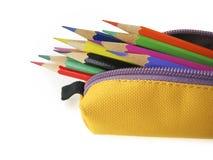 Färgblyertspennor i gul påse arkivbild