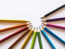 Färgblyertspennor i halv-cirkel på vitbok Arkivbild