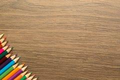 Färgblyertspennor med kopieringsutrymme som isoleras på träbakgrund arkivfoto