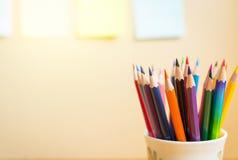 Färgblyertspennor med notepads på klar bakgrund Fotografering för Bildbyråer