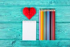 Färgblyertspennor och notepad Röd hjärtaorigami Arkivfoto