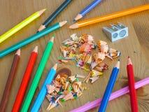 Färgblyertspennor och vässare på trätabellen royaltyfri foto