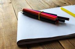 Färgblyertspennor på en vitbok arkivbilder