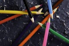 Färgblyertspennor på mörk bakgrund Arkivbild