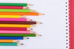 Färgblyertspennor på papper med anteckningsboken Arkivfoton