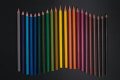 Färgblyertspennor på svart bakgrundsslut upp royaltyfri fotografi