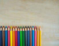Färgblyertspennor på trägolv arkivbild