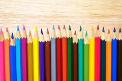 Färgblyertspennor på wood bakgrund Arkivbilder
