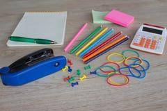 Färgblyertspennor, räknemaskin, anteckningsbok och kontorsbrevpapper på tabellen affärstillbehör på tabellen Arkivfoto