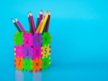 Färgblyertspennorna i färgrikt av blyertspennahållaren gör formen att förbrylla nummer på blå bakgrund äpplet books begreppsutbil Arkivfoton