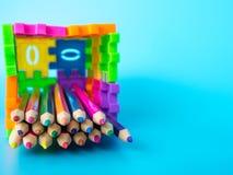 Färgblyertspennorna i färgrikt av blyertspennahållaren gör formen att förbrylla nummer på blå bakgrund äpplet books begreppsutbil Royaltyfri Foto